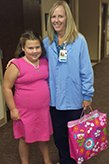 Avery Unruh, 8, recently donated coloring books and colors for children who are at Lawrence Memorial Hospital. Pictured with Avery is Traci Hoopingarner, director of Maternal-Child Services.